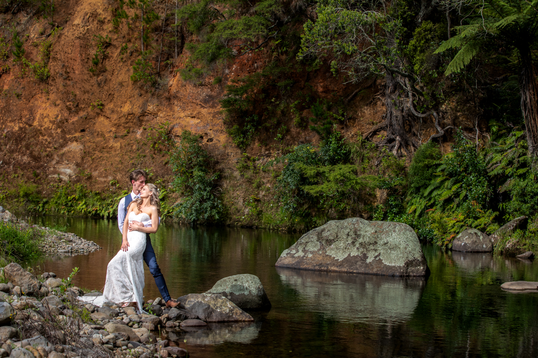 Bride and Groom embrace by the river