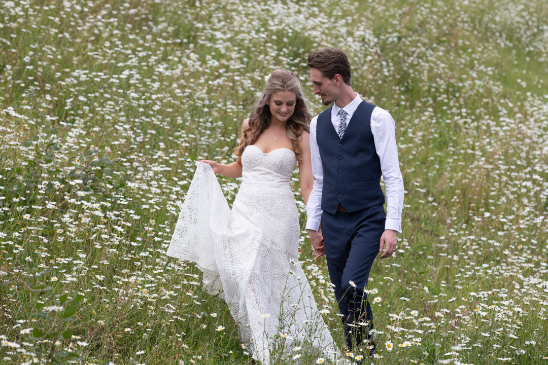 bride and groom walking in the daisy fields